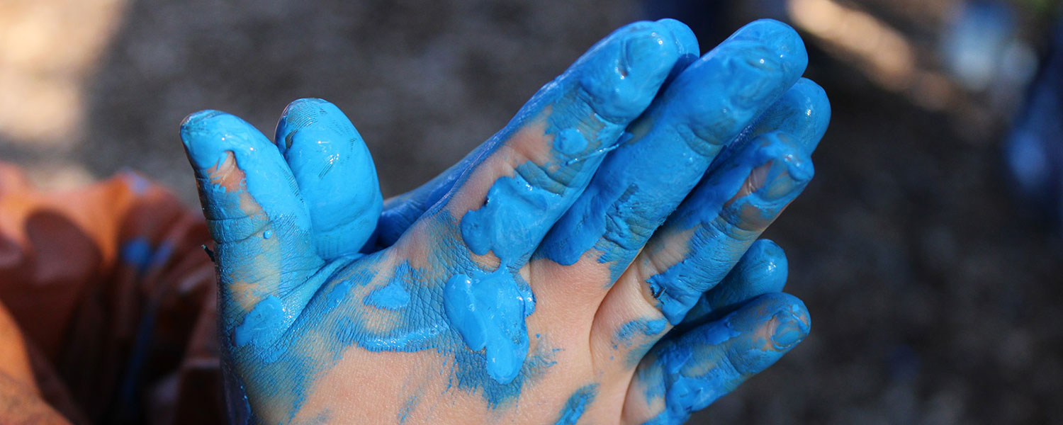child with blue paint on hands